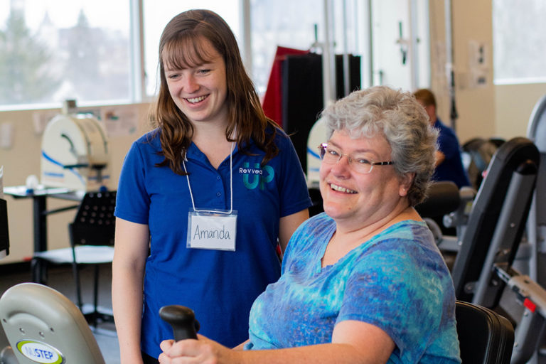 A breast cancer survivor exercising with a Revved Up supervisor