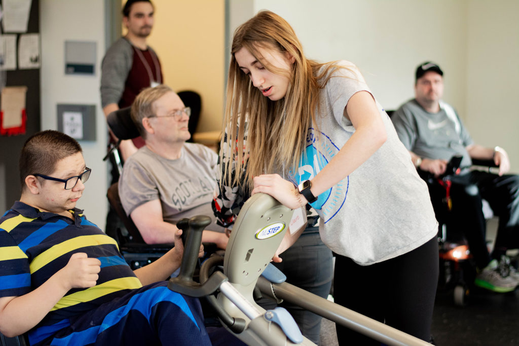 A student volunteer helping a program member with exercise equipment at Revved Up